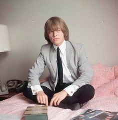 A portrait of Rolling Stones guitarist Brian Jones (1942 - 1969) sitting on a bed, London, 1964.