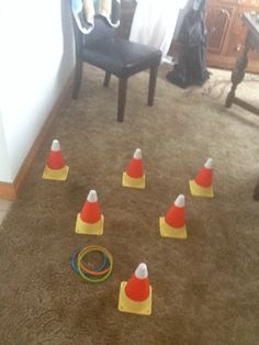 Candy corn ring toss. Paint mini pylons, found at the dollar store like candy corn, for the rings I used pool diving rings