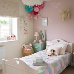 Girl's room in dusky pink with patchwork bed cover and pom pom light