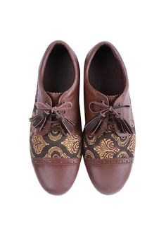 Saddle Brown hand-block printed Ajrakh fabric oxford in genuine goat leather with leather weaving on toe cap and an inner lining of faux leather Comes with a pair of geuine leather laces with tassels and genuine buffalo leather sole Perfectly designed to be paired with any casual/formal outfit, these are comfortable pair of shoes that can be worn with traditional Indian as well as western silhouettes. Fabric used for these is hand-block printed in natural vegetable dyes: Ajrakh printing...