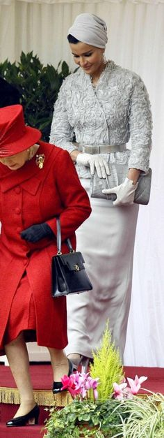 Sheikha Mozah of Qatar wore this fun turban in her trademark light gray, as seen outside of Buckingham Palace as she followed some old woman to a powder room.