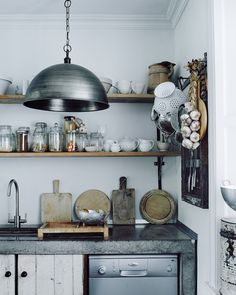 Stone work surface and wooden shelves in the kitchen of photographer Michael Sinclair.