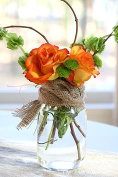 Mason jar with burlap, orange roses, baby's breath, bells of Ireland and twigs. center pieces for the head table.