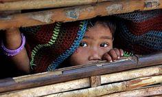 A Bhutanese refugee looks from a bamboo hut in the Ti Mai camp, Nepal.   Photograph: Desmond Boylan/Reuters