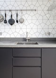 Contemporary kitchen featuring gray cabinets, granite countertops, stainless steel hardware and a unique geometric patterned tile as the backsplash | Trevor Brown Architect