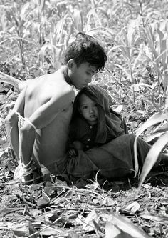 """A Vietnamese child clings to his bound father who was rounded up as a suspected Viet Cong guerrilla during """"Operation Eagle Claw"""" in the Bong Son area, 280 miles northeast of Saigon on February 17, 1966. The father was taken to an interrogation camp with other suspects rounded up by the U.S. 1st air cavalry division. (Richard Merron, Henri Huet/AP) ~ Vietnam War"""