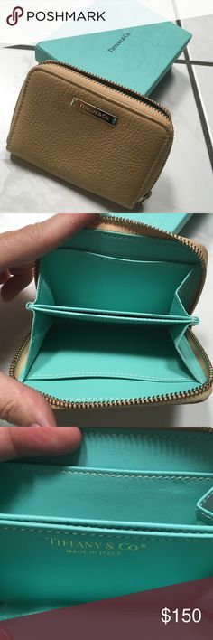 Authentic Tiffany wallet.💗host pick💞💗 Very cute authentic Tiffany wallet.  Used two times.    I bought and found another Wallet that I liked better. This one is just sitting around and needs a new home.  It is a tan leather with gold detail and Tiffany blue interior. Will come with box, but it is not in the greatest shape. 31/2 inches high  5 inches across Tiffany & Co. Bags Wallets
