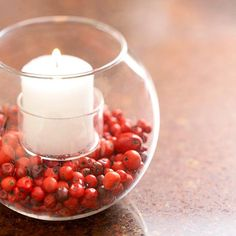 Fill a larger vase part way with fresh cranberries or small beads and insert a smaller glass votive holder.