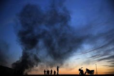 Kurdish refugees stand and walk on a hilltop as thick smoke rises from the Syrian town of Kobani during heavy fighting between Islamic State and Kurdish Peshmerga forces, seen from near the Mursitpinar border crossing on the Turkish-Syrian border in the southeastern town of Suruc in Sanliurfa province October 26, 2014. REUTERS-Yannis Behrakis