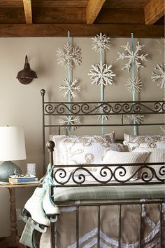 DIY snowflakes.  Love how they hung and displayed them behind the bed like this!