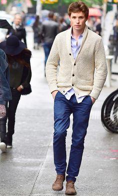 Eddie Redmayne wears a button-down shirt, knit cardigan, blue pants, and desert boots