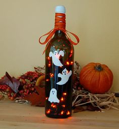 This wine bottle light is made from an upcycled wine bottle. A string of battery operated, amber lights is inserted through a hole drilled in the back of the bottle. The lights have a steady or twinkle option. Three ghosts are hand painted and heat set onto the bottle and an orange ribbon is added to the neck of the bottle.    Requires 3 AA batteries. Batteries not included.