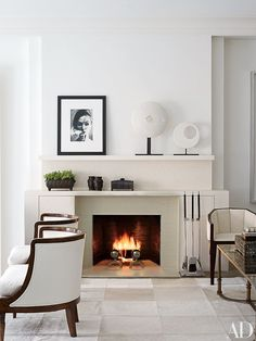 The living room of a New York City apartment, which was decorated by Penny Drue Baird of Dessins, serves as a gallery for works by, from left, Damien Hirst, William Klein, and Hiroshi Sugimoto. The angular armchairs are 1930s French, the barrel-back bergères are from Lee Calicchio, and the cowhide rug is by Stark Carpet | archdigest.com