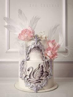 Pretty baroque inspired wedding cake with silver framing, hand painted swans pink sugar flowers and wafer paper feathers.