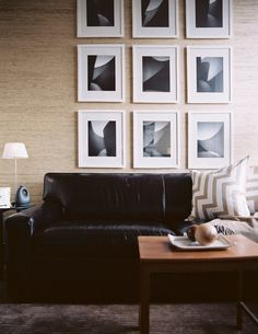Sand beige grasscloth wallpaper, white gallery frames, black leather sofa, taupe zigzag chevron silk pillows and chocolate brown rug. Living Room Photos, Home Living Room, Living Room Decor, Living Spaces, Black Leather Sofas, Black Sofa, Urban Decor, Living Room Inspiration, Design Inspiration