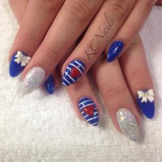 Royal blue, white, and red nails.  Almond shape with white 3D bow. Hand sculpted red heart and painted white striped nail art.  KCNails