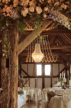 Crystal wedding chandelier with a fairy light canopy at the beautiful Loseley Park Tithe Barn. Wedding lighting by Oakwood Events Ltd.
