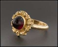 Garnet, the birthstone of January, is said to symbolize constancy and truth. This gorgeous ring features a gold wreath surrounding a stunning high garnet cabochon. The face of the ring was originally a 14k gold stick pin, and we welded it onto a vintage 14k gold band to transform the piece into a ring.  The face of the ring measures 0.6 inches (14mm) in diameter and is in excellent condition. The ring is currently a size 6.75, but it can be re-sized free of charge. We have many other…
