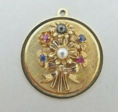 """Vintage 14K  DANKER Yellow Gold Round Flower Bouquet Garnet Sapphire Pearl Charm Pendant  This charm has a flower bouquet in the center with 4 gemstones and 2 pearls.  The stones are garnet and sapphire and the center pearl is white and the top pearl is gray/black.  The back of this piece is marked 14K with the Henry Dankner signature wreath with a """"D"""" in the center.  This charm pendant measures 1.125"""" and weighs 8.2 grams.  It's a fabulous example of 1960's chunky, jeweled style. Silver Pendants, Gold Pendant, Lipstick Case, Sapphire Pendant, Jewelry Bracelets, Jewellery, Vintage Jewelry, Charmed, Pearls"""