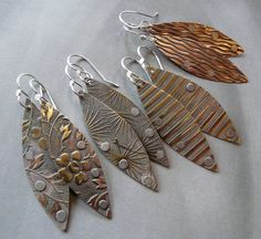 Patterned brass and copper earrings with aluminum rivets.