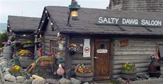 The Salty Dawg, a bar located in Homer, Alaska, started out as one of the first cabins built in 1897, soon after Homer became a town site. It served as the first post office, a railroad station, a grocery store, and a coal mining office for twenty years. In 1909 a second building was constructed, and it served as a school house, post office, grocery store. And at one time, it housed three adults and eleven children.