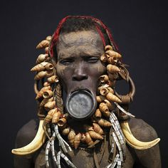 Ethiopia by Eric Lafforgue, - Ethiopia  Piercing, labret, and lip plates are a strong part of the Mursi and Surma -Suri culture.  When a woman becomes engaged (at 14 or 15),  The gap between her front lip and the flesh below is pierced and gradually stretched. The final size of the plates determines how many cattle she will receive as a dowry. Although it is seen as a sign of beauty nowadays, it is said that the disfigurement began as a way to prevent slavers from seizing Suri women.