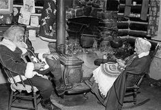ca. 1935-1950 --- At home with Mr. and Mrs. Claus (Clarke and Elizabeth Chaplayne). The couple who dress as the revered Christmas giftgivers are shown seated at home, him smoking a long pipe and her knitting on a rocking chair. Undated photograph. --- Image by ? Bettmann/CORBIS