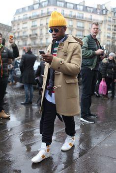 Mann trägt auf der Straße einen beigen Mantel