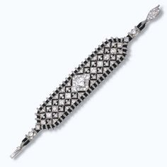 AN EXQUISITE ART DECO BRACELET, BY CARTIER  Of geometric diamond openwork design with a central cushion-shaped diamond to the black silk cord frame and velvet backing, circa 1925, 16.0 cm long, with French assay marks for platinum and gold Signed Cartier, no. 5009