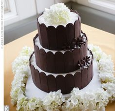 Chocolate scalloped panels lined each tier of the white cake, which was topped with chocolate flowers and white hydrangeas.
