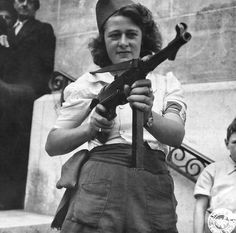 """In a Signal Corps photograph, a French resistance fighter whose nom de guerre was """"Nicole"""" poses with a captured German MP40 submachine gun on August 23, 1944 after the liberation. She was credited with capturing 25 Germans and killing several more in the Chartres area."""