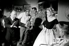Alfred Hitchcock setting a scene for Grace Kelly and James Stewart during the filming of Rear Window, 1954