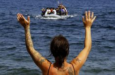 A volunteer signals at a dinghy with Afghan migrants at a beach on the Greek island of Lesbos, after the dinghy crossed a part of the Aegean Sea from the Turkish coast September 21, 2015. REUTERS/Yannis Behrakis