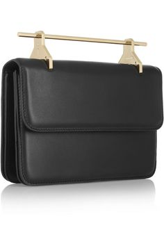 "Minimalism, surrealism, world architecture and history all inform Barcelona-based duo M2Malletier's aesthetic. This handmade black leather clutch features the brand's signature gold ""needle"" handle inspired by medieval armor and tools. Wear it as a shoulder bag using the optional strap. x"