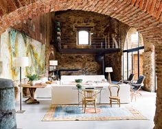 wow, nicely done. brick archways, stone walls, huge windows, reading loft - via nuevo estilo