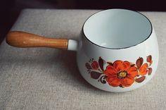 Cudny rondelek emaliowany. Biały, w idealnej kondycji. Z drewnianą rączką (na której w jednym miejscu widoczny ubytek lakieru). Z dwóch stron kwiatowy wzór w kolorach pomarańczu i brązu. Wymiary: obwód 50 cm, dł. rączki 14 cm