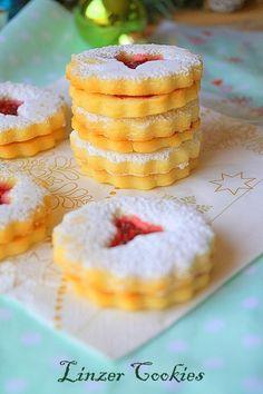 Linzer cookies recette facile. Voici une douceur bien gourmande Linzer cookies ou bredele à la confiture de framboises, des biscuits sablés fondants et croquants à la fois inspirés de la Linzer torte autrichienne confectionnés traditionnellement à l'occasion de Noël en Allemagne, Alsace et aux Usa ! Une simple pâte sablée sucrée friable aux amandes, parfumée avec un soupçon de cardamome et garni de confiture de framboises faite maison (c'est tellement meilleur), le tout orné d'un nuage de sucre Cheesecake, Eid, Occasion, Decor, Cookies, French Food, Decoration, Cheesecakes, Decorating