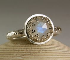Rainbow Moonstone set in a solid sterling silver fancy bezel setting. I have several of these beautiful little stones available for custom