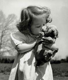 Menininha beijando seu filhote e fazendo carinho nele.