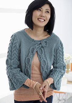 This beautiful cardigan combines a clean neckline with an intricately-cabled button band.