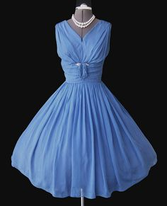 1960s chiffon blue cocktail dress.  Full skirt; cinched/ruched midriff with tassel accent.  Shirred bodice with 'V' neck; sleeveless.  Looks great with pearls.