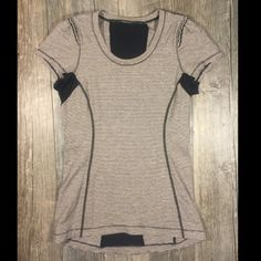 Lululemon black off white stripe & ruffle tshirt Lululemon black and off white stripe and ruffle tshirt. 27 inches long. Black mesh panel on back and under arms. Ruffle accent on sleeves. Tag has been removed, see lululemon logo pic. 29 inch waist and bust is 32 inches approximately before stretch, shirt has stretch, according to their website its closest to 4. lululemon athletica Tops Tees - Short Sleeve