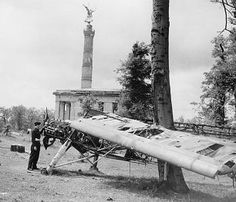Fieseler Fi-156C Storch. The only available picture of Hanna's Fi-156. It shows the Storch placed behind the Brandenburger Tor Siegessäule in the background and guarded by a British soldier.  badly damaged when the picture was taken. In addition to the damages inflicted by Soviet AAA, it was most probably hit several times when parked on the ground.   And obviously, souvenir looters also had a field day before the picture was taken.