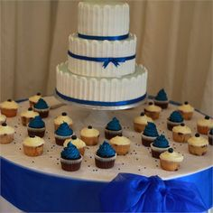 a three tier wedding cake which featured a pretty blue ribbon  Mini cupcakes were also dotted around the cake