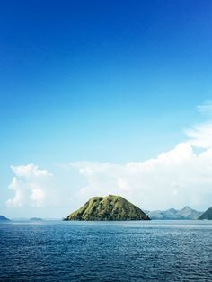 """One of Komodo National Park's 29 islands. This beautiful reserve was established in 1980 and was declared a UNESCO World Heritage Site in 1991.The blue water, green hills, and ever changing clouds... We'll never tire of this view. The Indonesians have a different word for describing landscape as beautiful. They use indah.For a beautiful girl they use cantik(pronounced """"chan-ti"""")."""