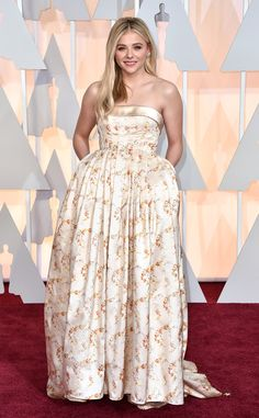 2015 Oscars: Red Carpet Arrivals - Chloë Grace Moretz attends the Academy Awards Ceremony in a beige/white gown with brown designs in the gown designed by Miu Miu.