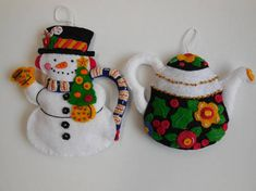 Made from a 2004 Bucilla kit, these ornaments were designed by Mary Engelbreit. The snowman measures approximately 5 1/3 x 4 1/2, and the black pot measures approximately 3 3/4 x 4 1/2. Stuffed for a 3-D effect, they are completely hand-sewn with lots of aloha. No glue or machine