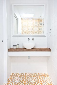 Love this small bathroom design with floating white counter topped with unfinished reclaimed wood counter top, small white basin sink, wall-mounted silver sink faucet, and gorgeous dark yellow, tan and white printed Spanish-inspired tiles on the floor and Laundry In Bathroom, Bathroom Renos, Bathroom Interior, Bathroom Ideas, Bathroom Styling, Bathroom Storage, Tiny Bathrooms, Counter Top Sink Bathroom, Modern Bathrooms