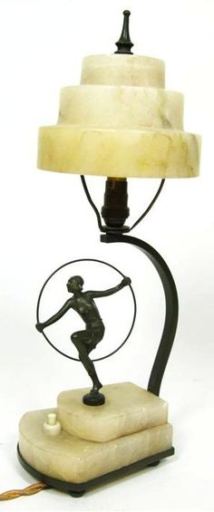 ART DECO  SPELTER AND ALABASTER TABLE LAMP, 1920S  the cylindrical stepped shade with curved bracket support on stepped base surmounted by a dancing figure  36cm high