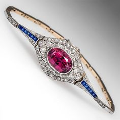 Victorian Bracelet Pink Tourmaline & Diamonds 14K Gold & Platinum 1880's. This gorgeous 1880's Victorian era bracelet features a centered oval cut tourmaline bezel set into a diamond encrusted pierced and milgrained plaque. The tourmaline is accented with rose and Swiss cut diamonds and square cut lab created blue sapphires. The bracelet is crafted of solid 14k yellow gold and the center plaque is topped in platinum while the bracelet links are topped in 14k white gold.